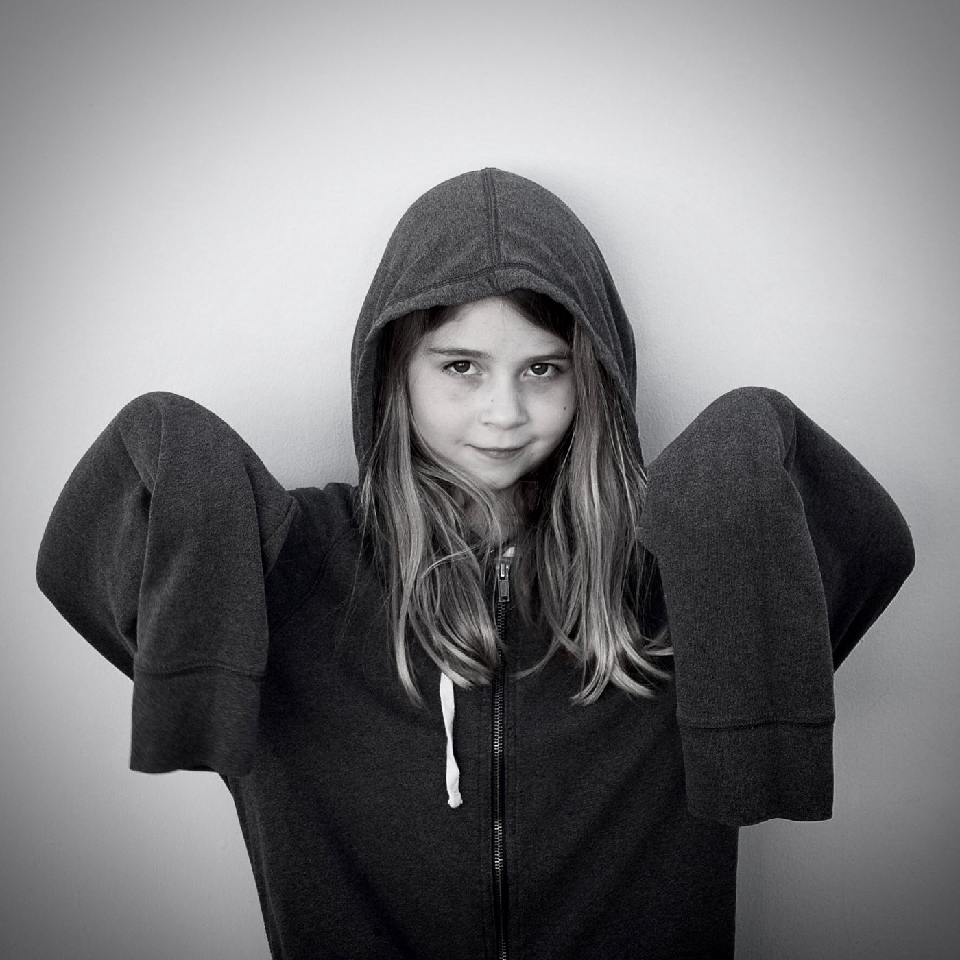 a little girl wearing a big sweatshirt