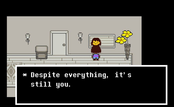 """Screenshot of Frisk from the video game Undertale. They are standing in front of a mirror in a black-and-white hallway, a vase with golden flowers to their right. The text reads """"Despite everything, it's still you."""""""