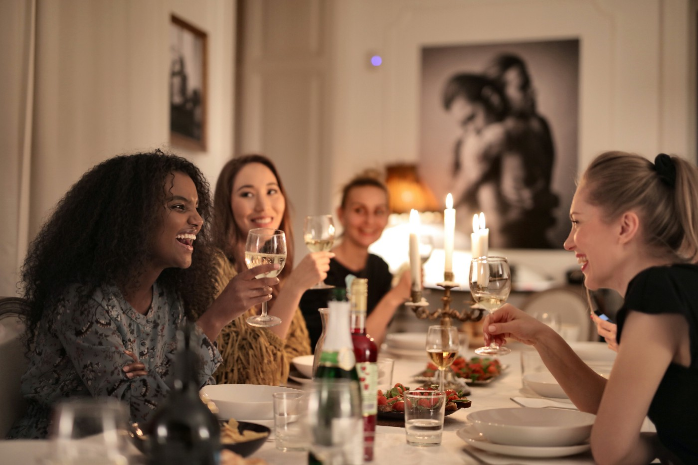 Women Holding Wine Glasses and laughing. They're at a candlelit dinner party.