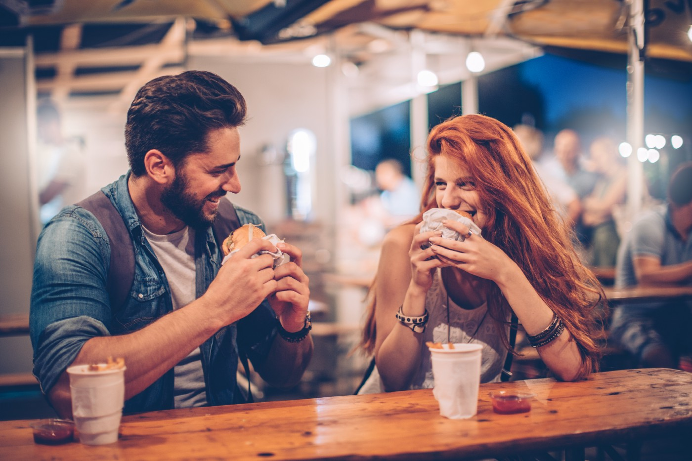 A man with dark hair and a beard sits with a woman with long, red hair. They are eating and smiling at each other, clearing enjoying being in each other's company.
