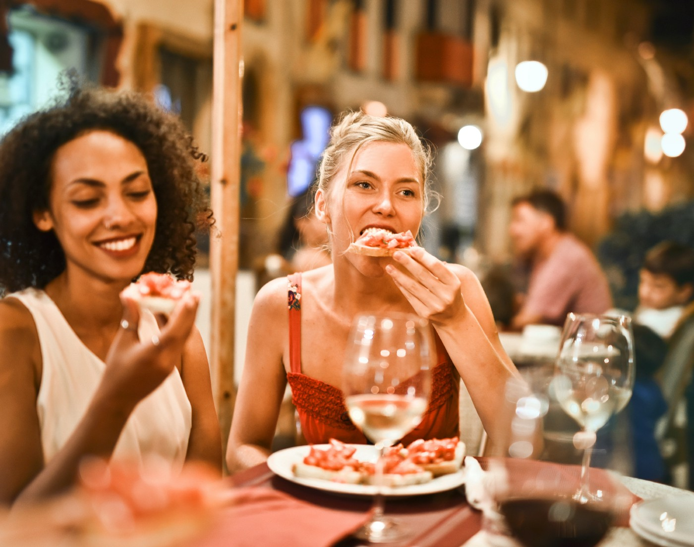 Two people sit at a table in a restaurant eating pizza.