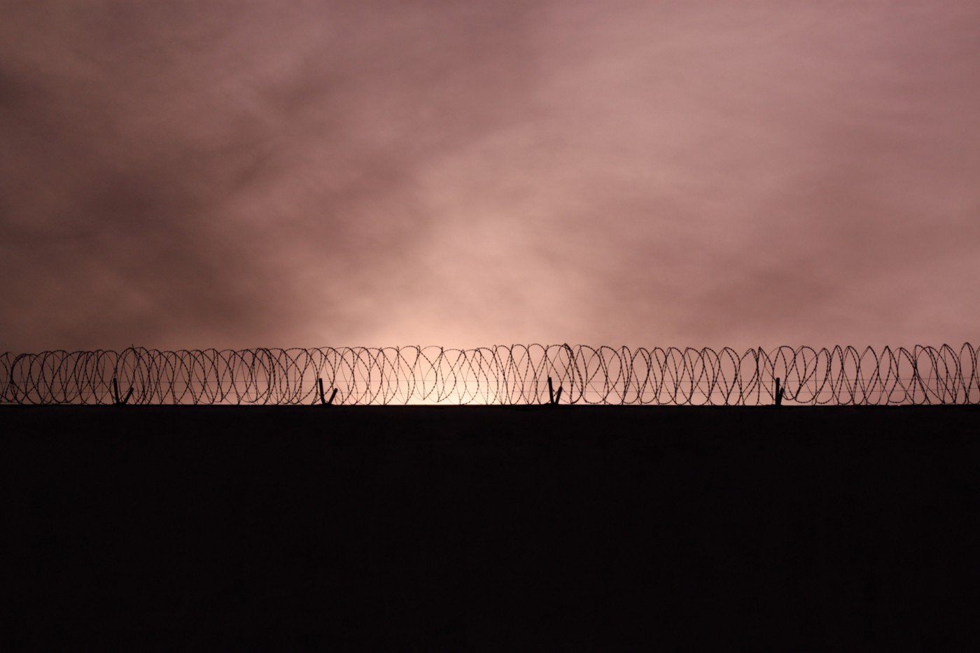 A photo of a barbed wire fence against a sunset sky.