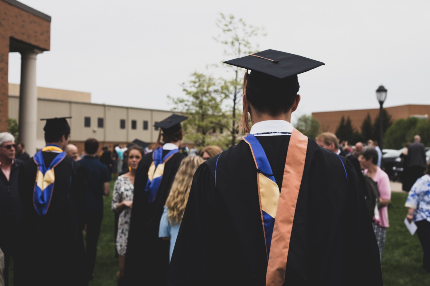 A student in a graduation gown with his back turned to the camera