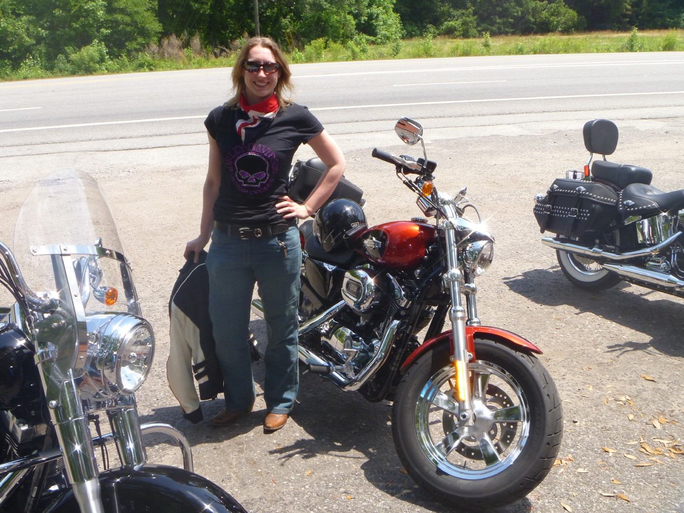 A woman stands in front of three motorbikes