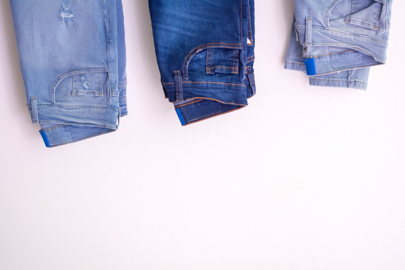 three pairs of denim jeans on an off-white background