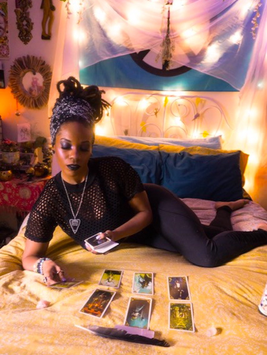 Photo of Jamila Anahata, wearing a witchy black outfit, looking at her tarot spread while reclining on a yellow bed
