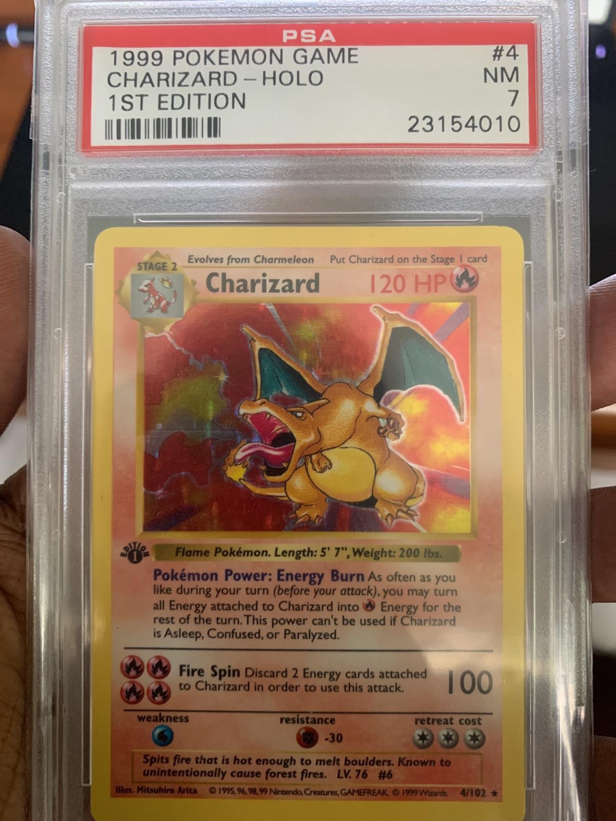 My Friend's Charizard Card, encased and graded with score 7 | photo taken by author