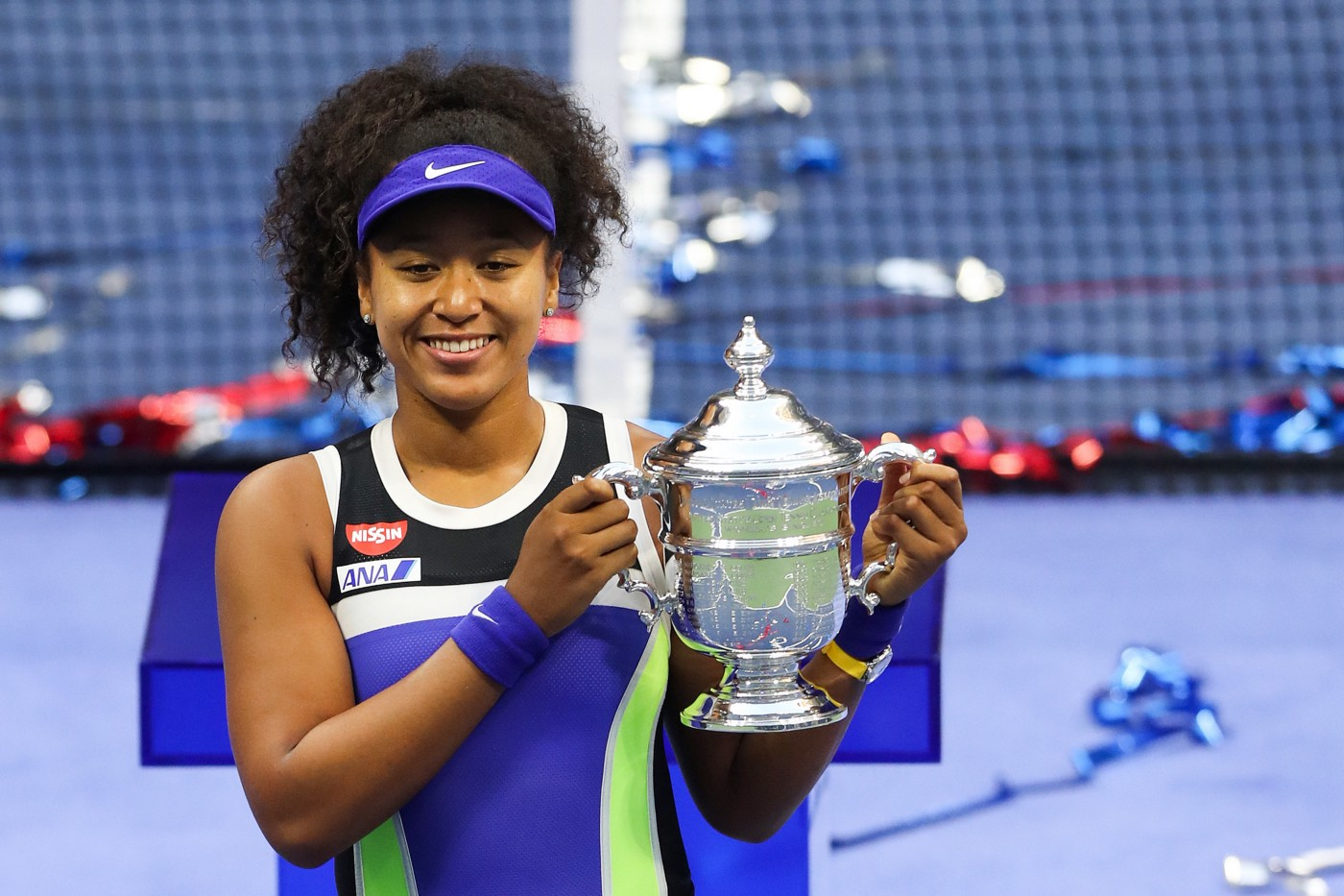 Head to mid body shot of Naomi Osaka, wearing bright blue and green athletic clothing, holding a trophy from a tennis tournament, and smiling.