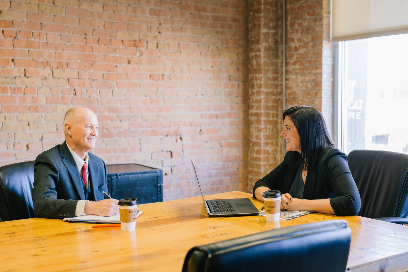 meeting in board room with middle aged man and young woman in business suits