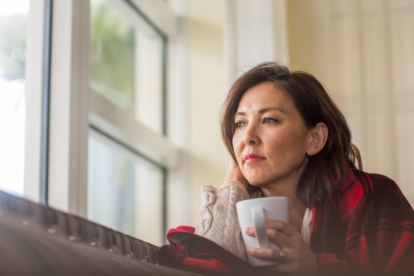 A woman holding a cup and looking out the window thoughtfully.