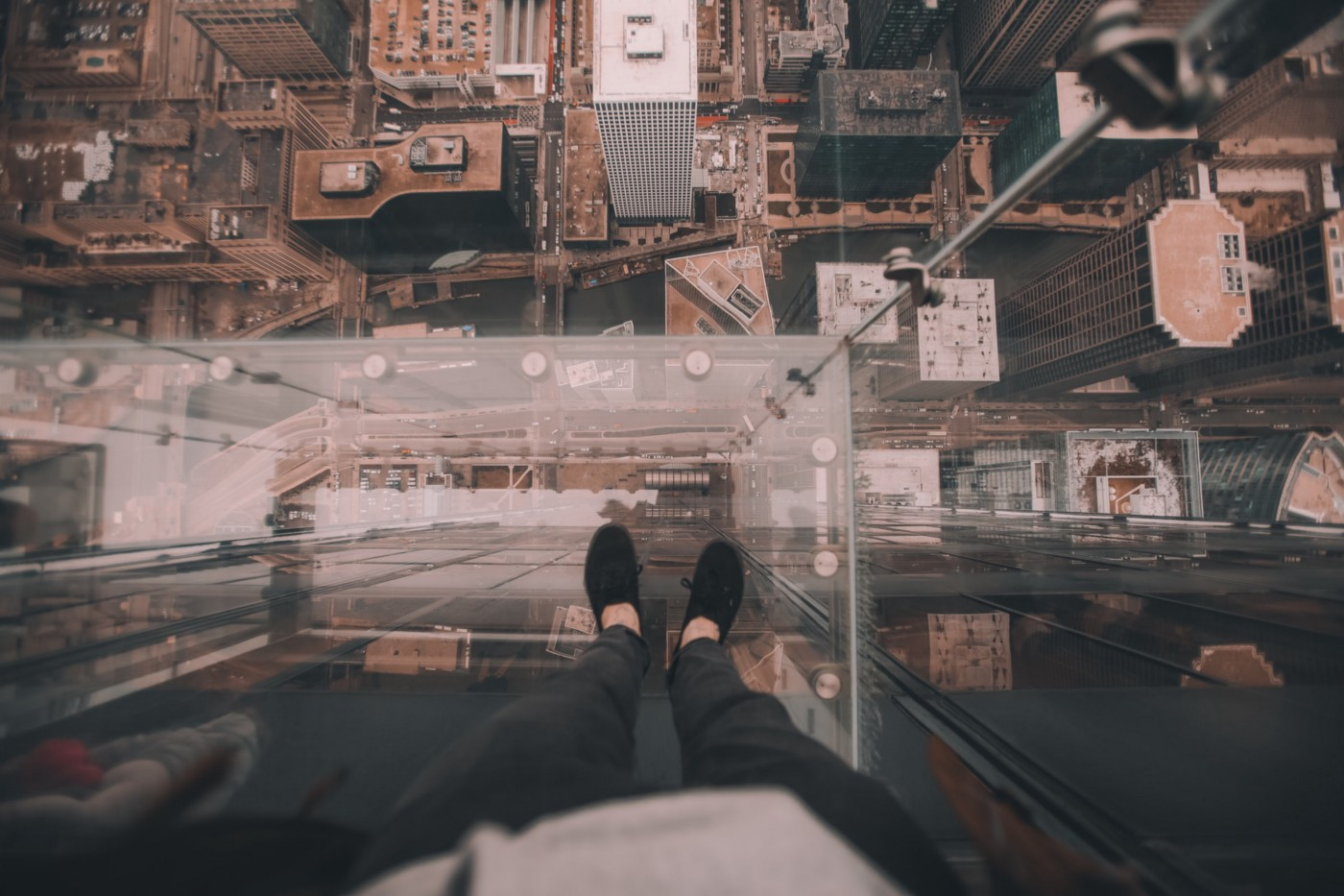 Someone standing on a glas ceiling looking down on their feet and the city beneath them from an ego perspective.