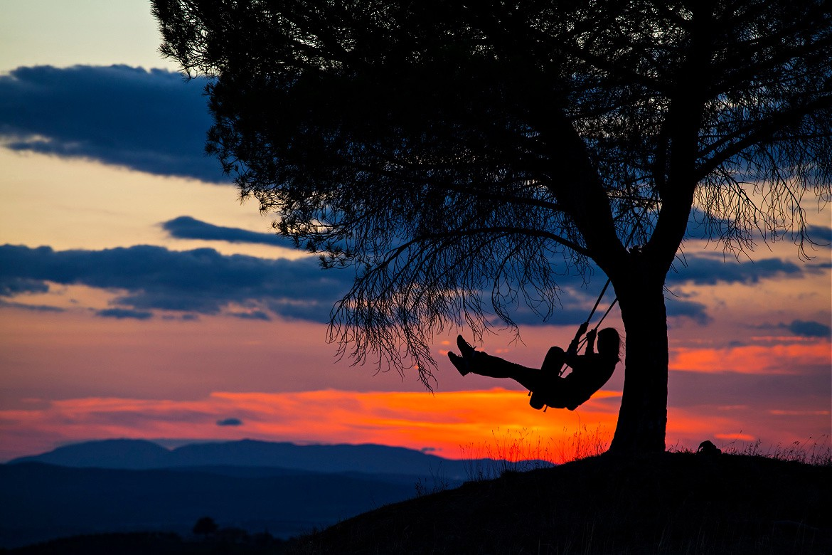Silhouette of a girl on a tire swing, under a big tree with a red sunset sky.