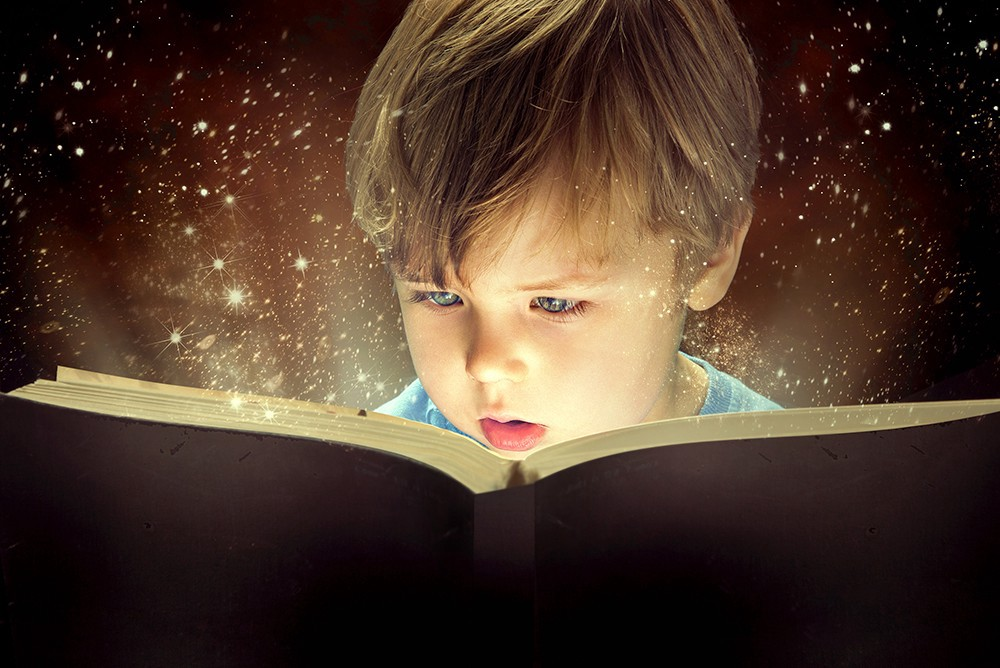 A young boy reading a book with sparkles coming out