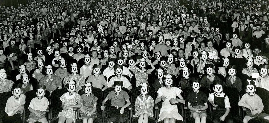 an auditorium full of people in creepy masks