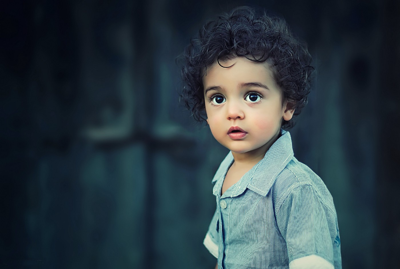 Toddler with brown hair staring at the camera. Dark blue wall in the background. Toddler is wearing a blue shirt.