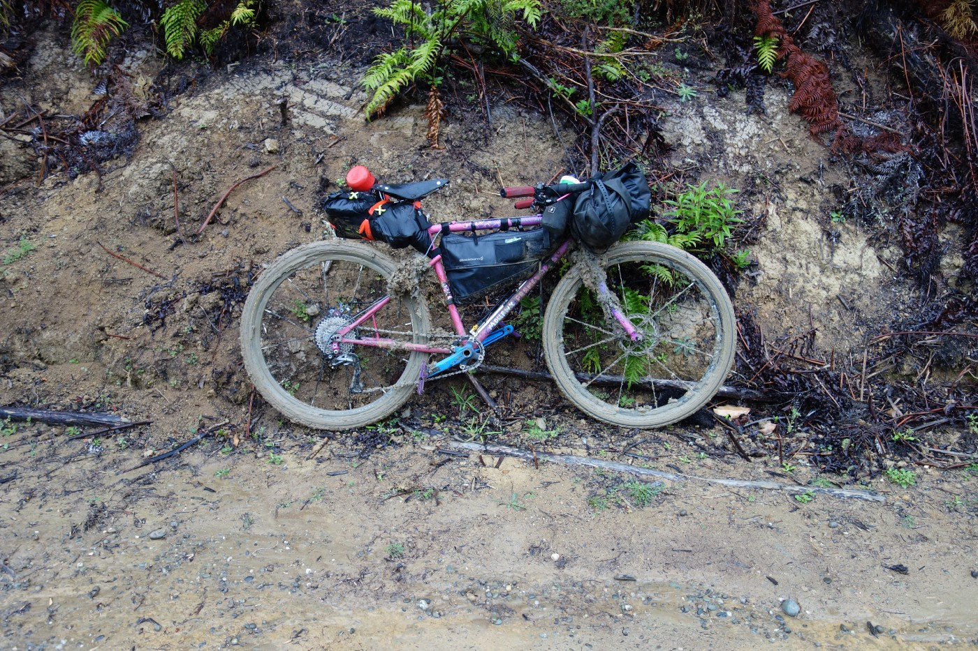 Sarah's bike is leant against a muddy bank. The wheels are completely clogged with thick mud.