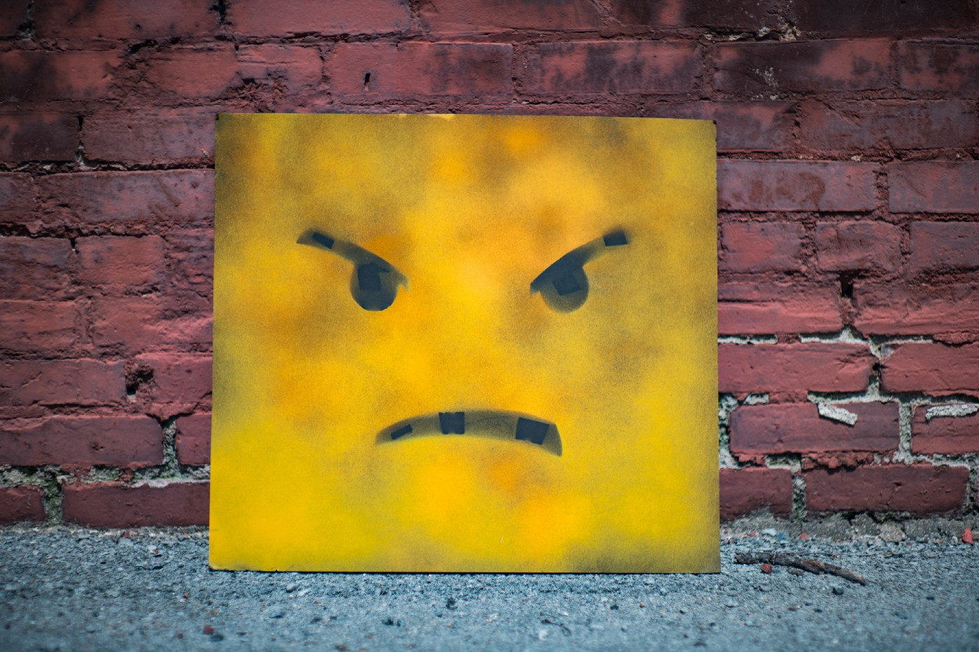Yellow box with an angry face against a brick wall.