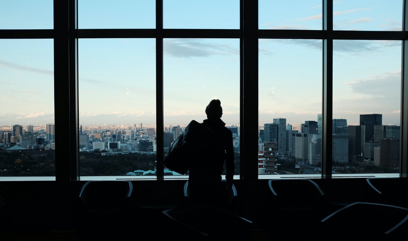 Silhouette of a woman in a high rise office staring out over a city skyline.