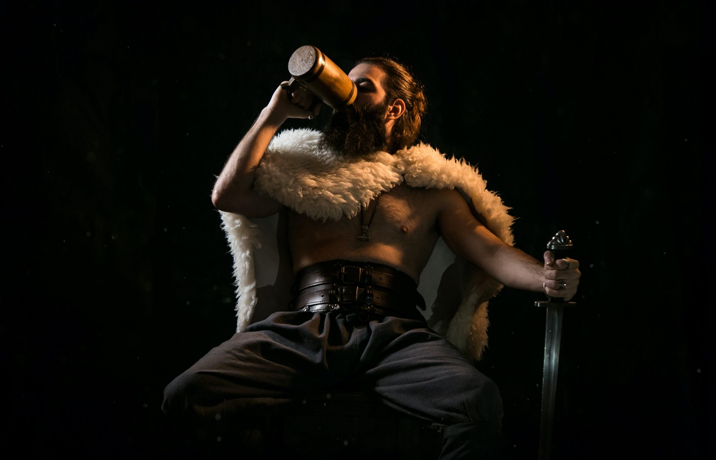 A man drinking from a mug and holding a sword. Portrait of a Reluctant Hero by Jim Latham in Jim's Shorts.