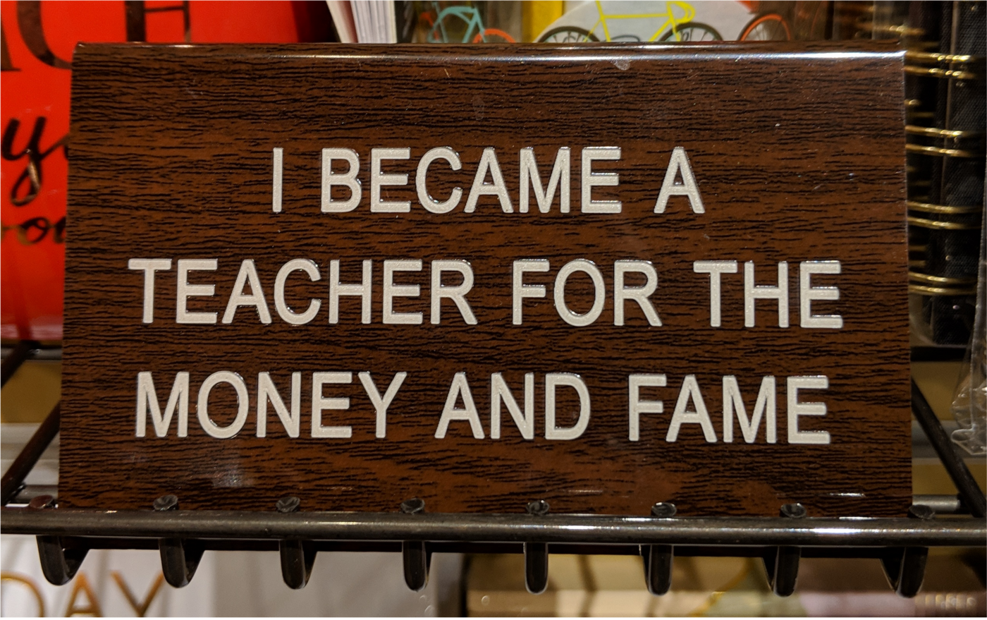"""A placard reads: """"I became a teacher for the money and the fame."""""""