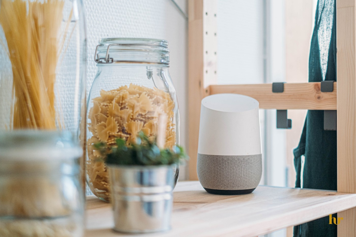 Image with a voice assistant sitting besides a jar of flakes.
