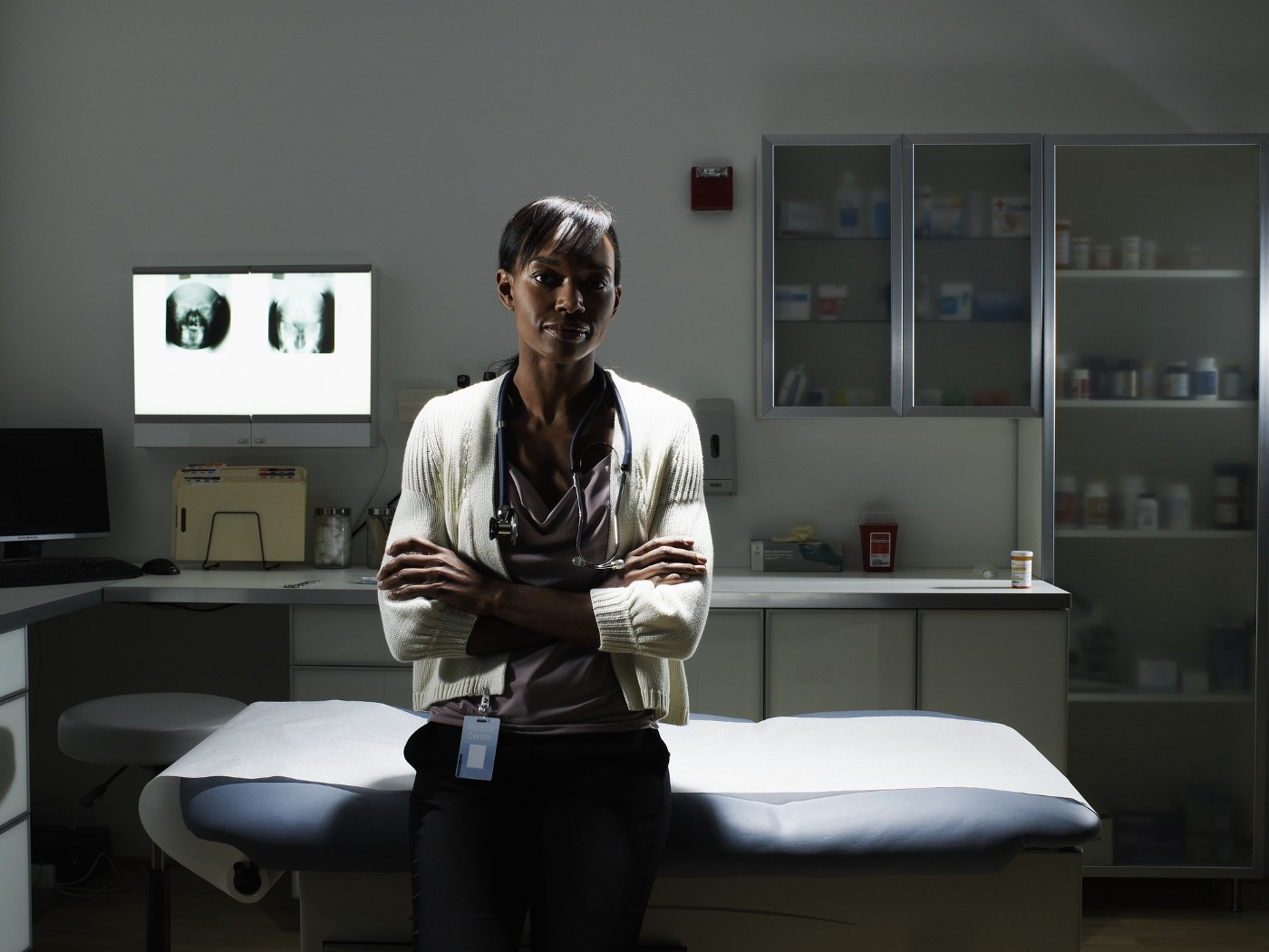 A photo of a Black female doctor sitting in an examination room, arms crossed.