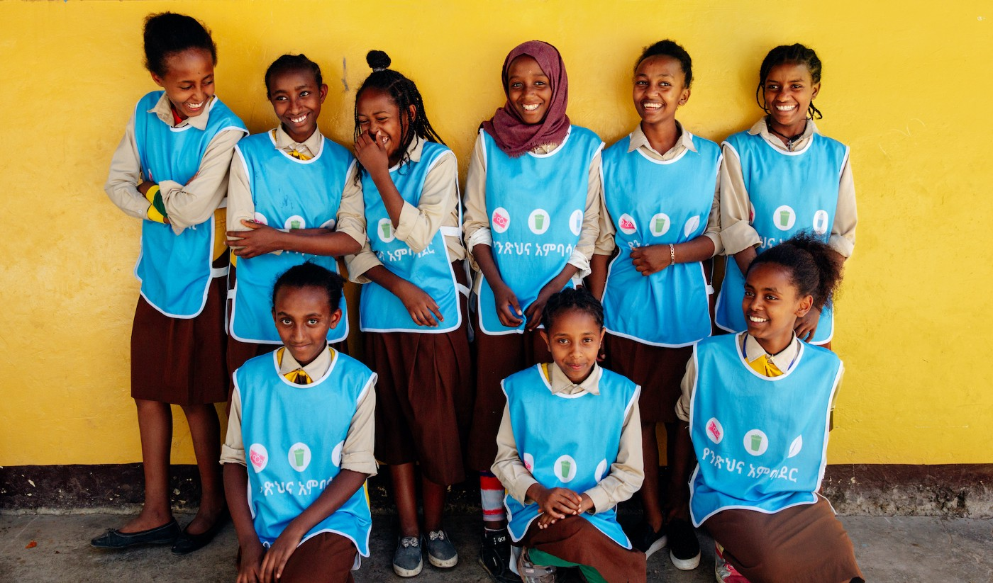 A group of girls in Splash vests smile and giggle in front of a yellow wall at school in Addis Ababa, Ethiopia.