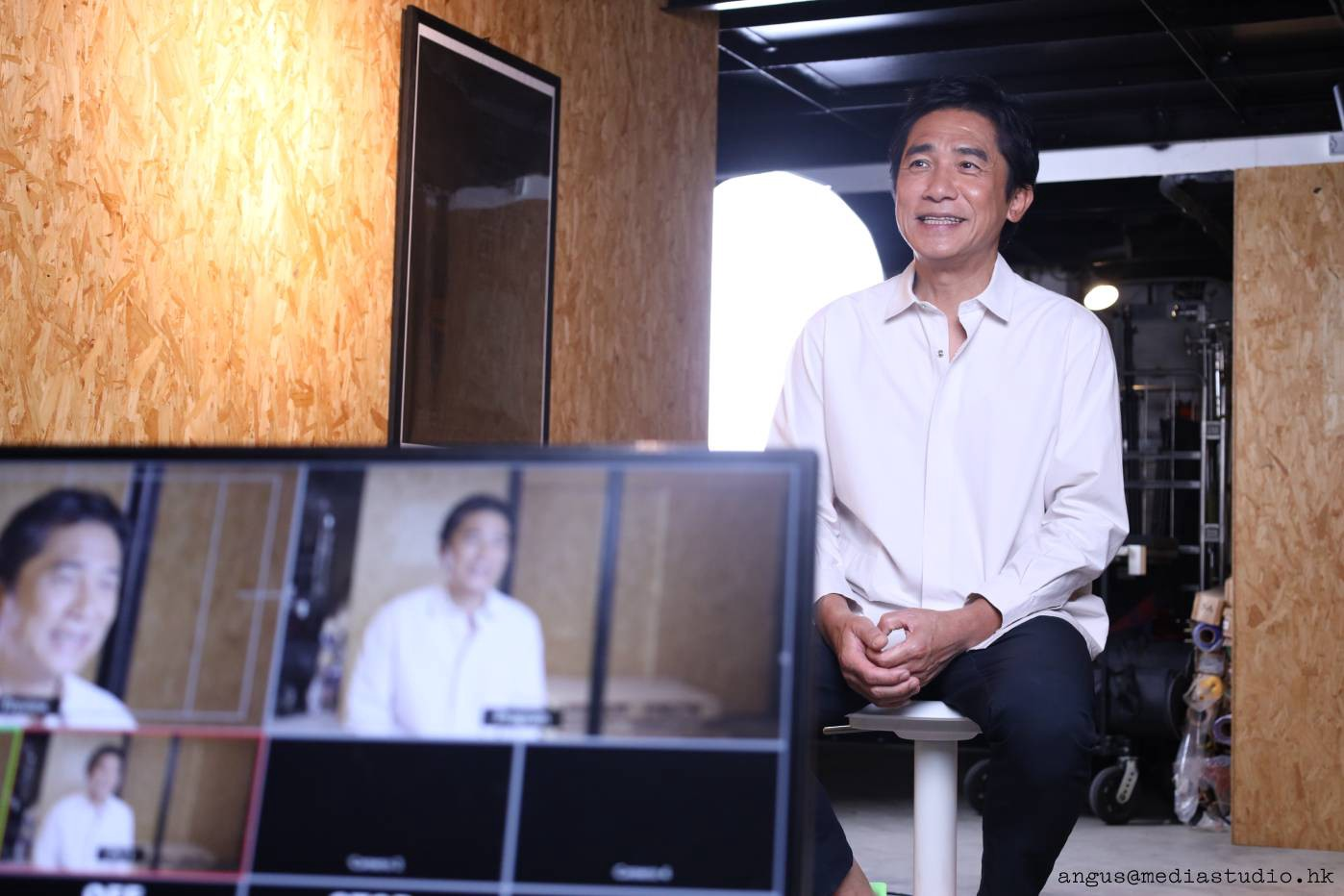 Tony Leung Chiu-wai sitting on a chair for an interview inside a warehouse. A screen shows different camera angles on Tony.