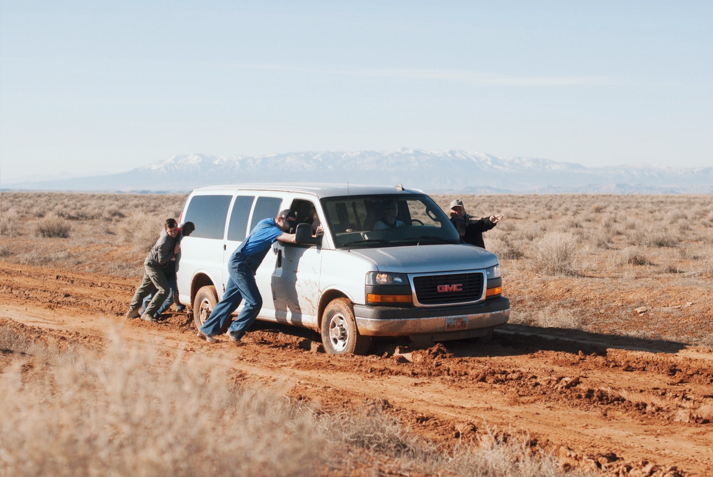 Old white econoliner-type van stuck in the mud in a remote area being pushed by three people