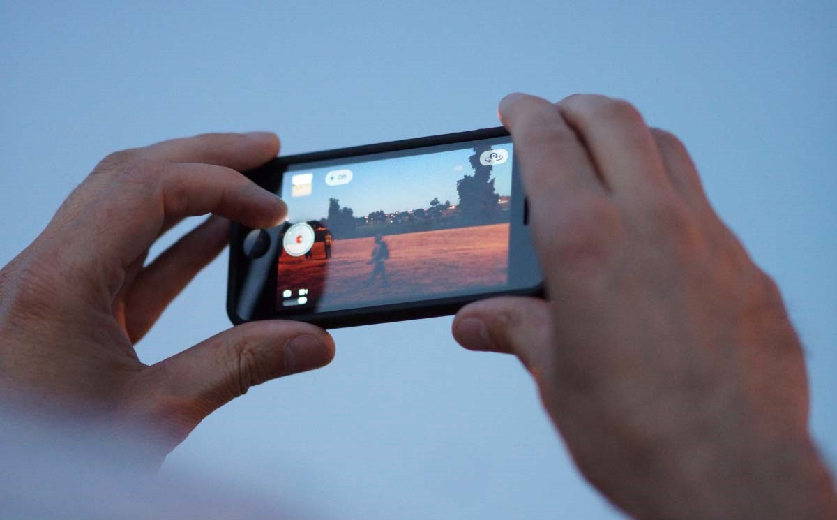 Hands holding up smartphone to record video