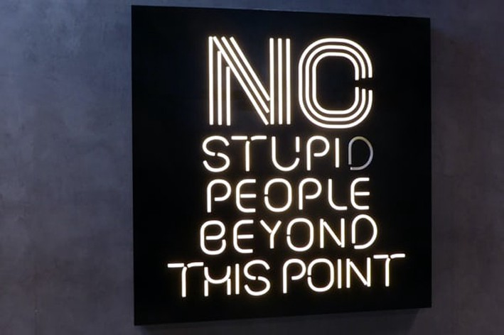 "A neon sign saying ""No stupid people beyond this point."""