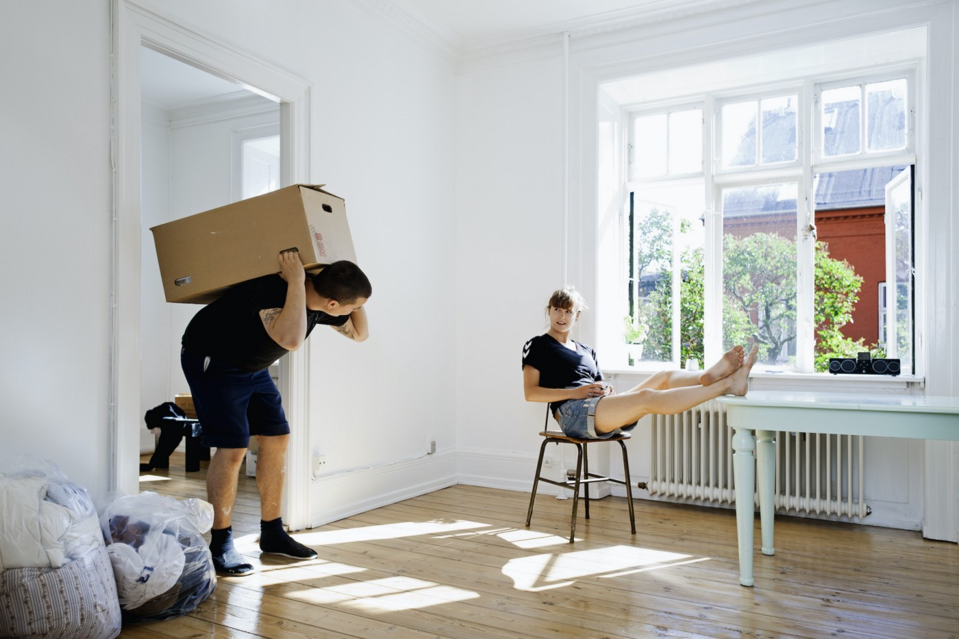 A mover carrying a box on their back, looking at a person with their feet on a table next to an open window.