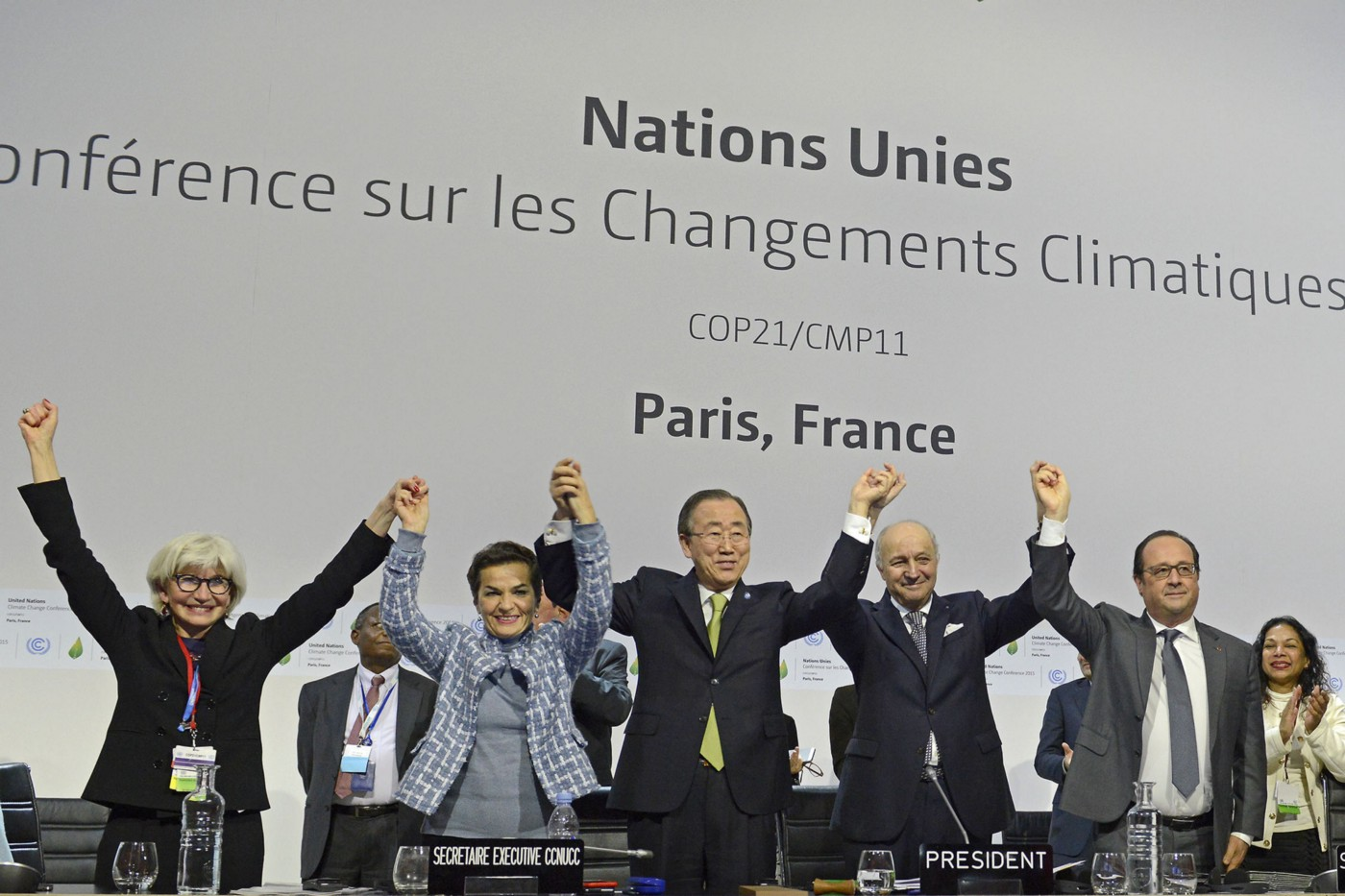 World leaders raise their hands in celebration after signing the Paris Climate Agreement.