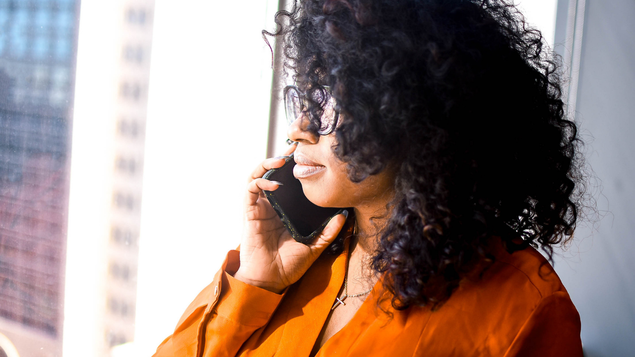 Black woman with curly black hair and a copper colored blouse looks out of a window while holding a cell phone to her right ear.