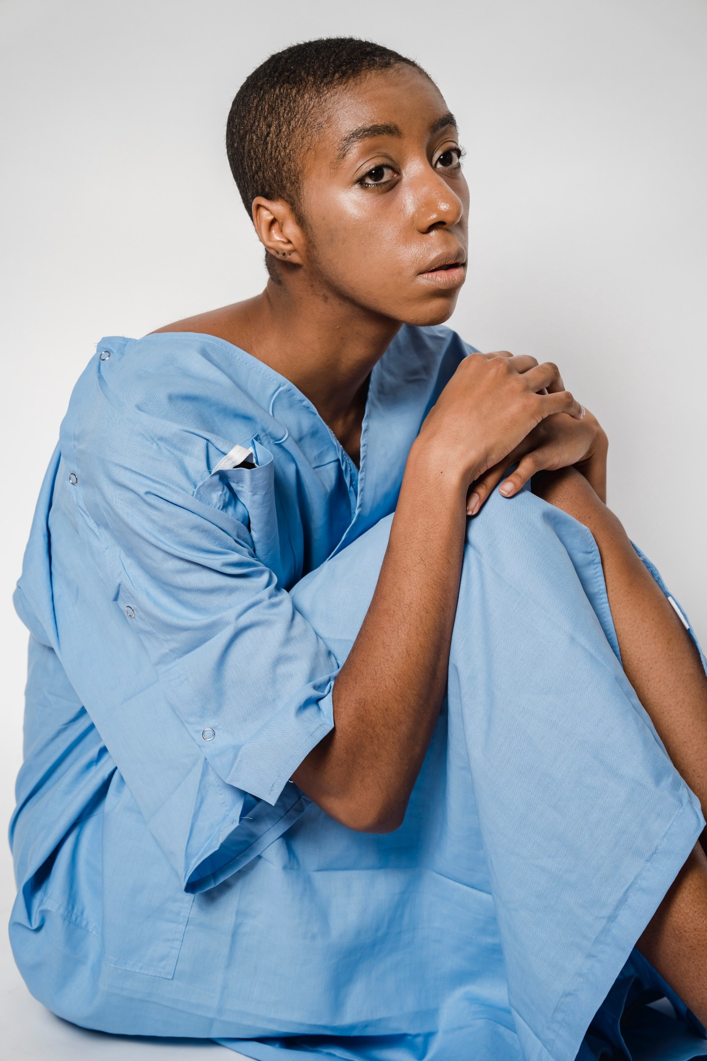 A person in a blue hospital gown sits with a dazed, distant look and their hands crossed on one bent knee.