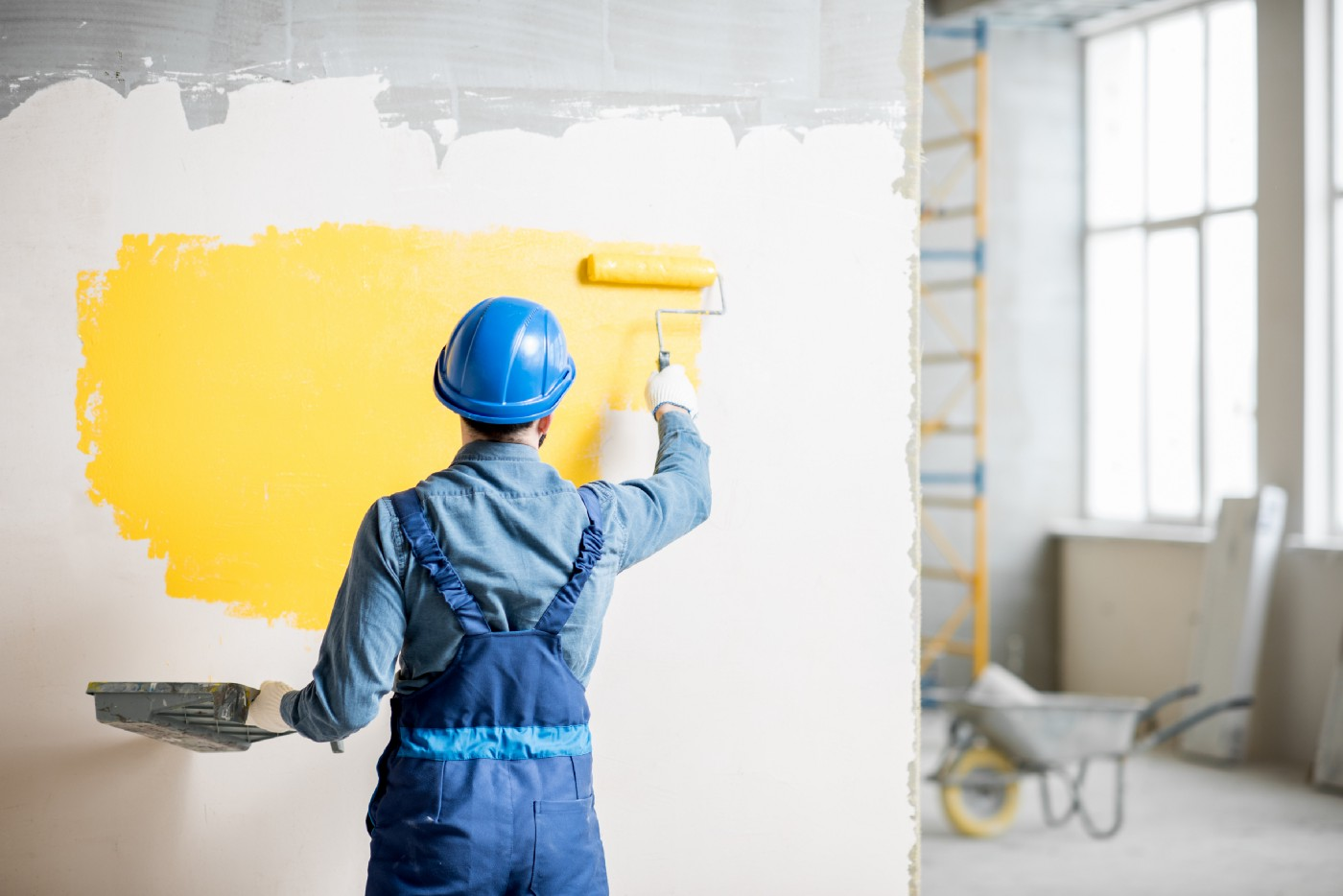 A workperson is painting yellow over a white wall with ragged gray coloring at the top.