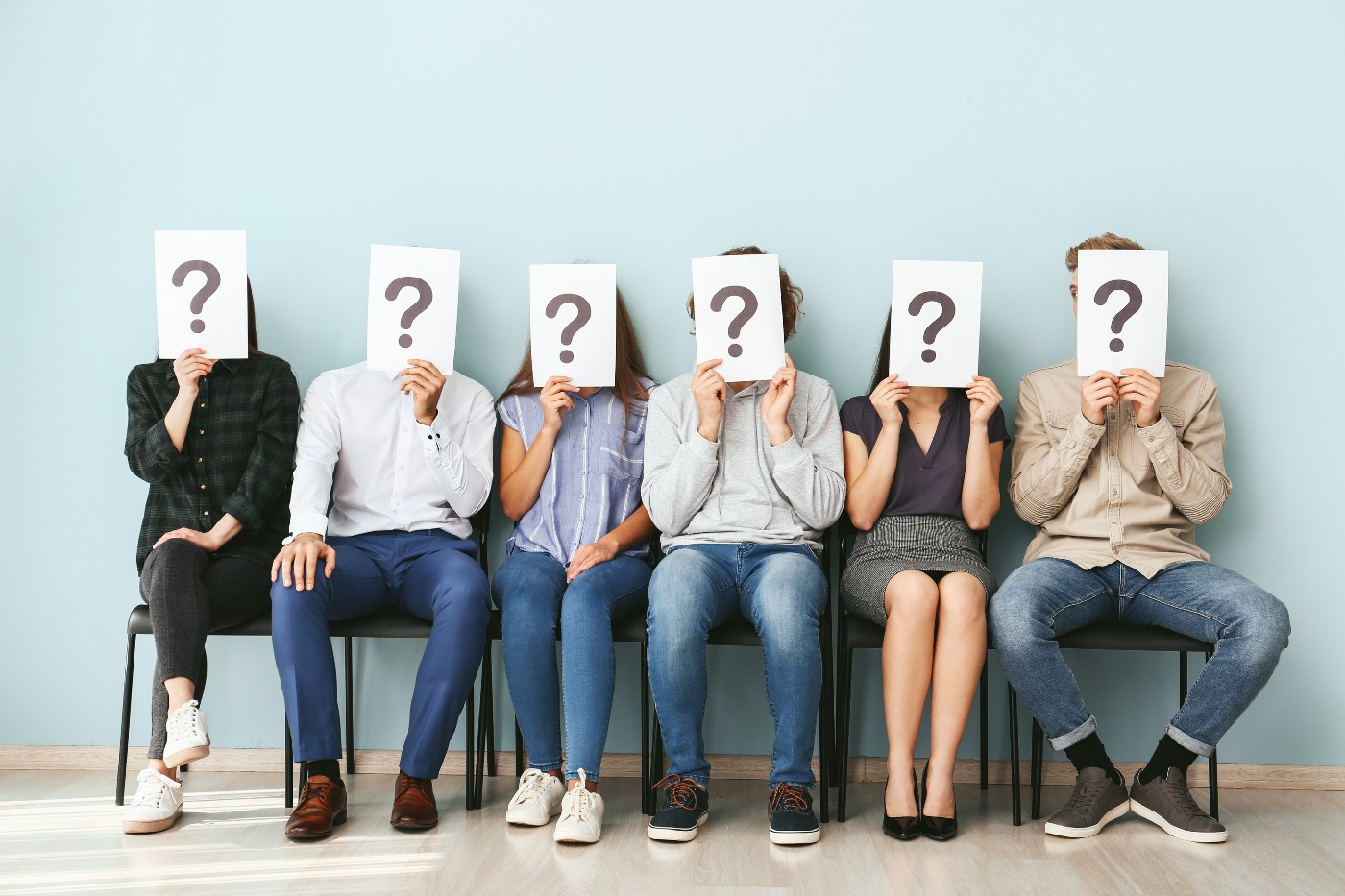 Employees sitting holding papers with question marks over their faces