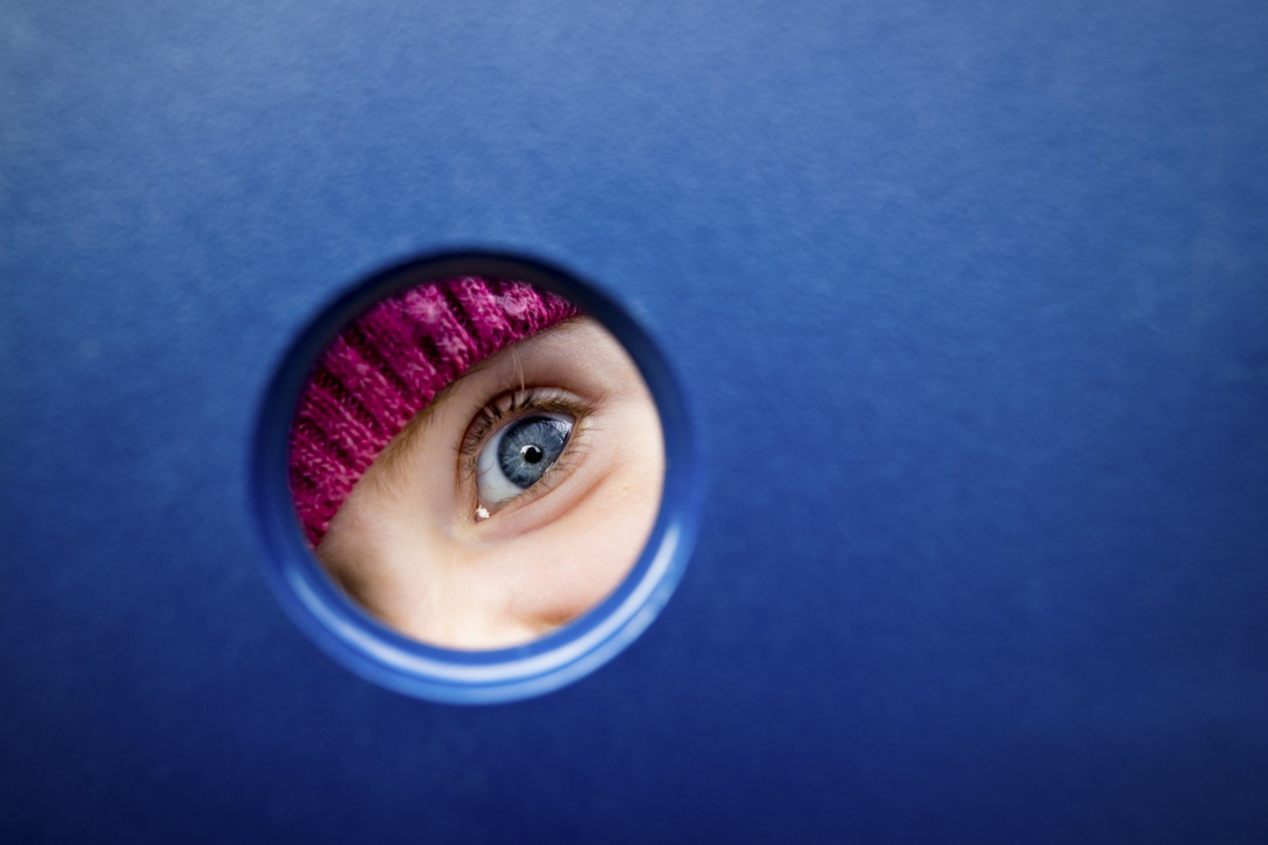 A photo of a young girl's eye peering through a hole in a blue wall.