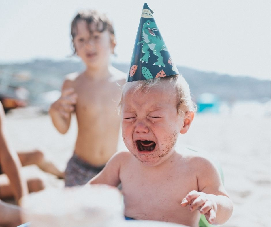 A baby with a birthday hat is crying at the beach