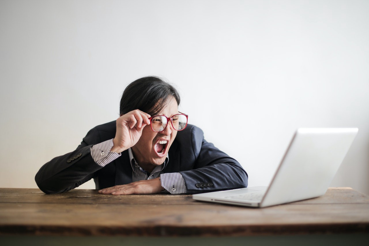 Businessman staring at computer screen in disbelief.