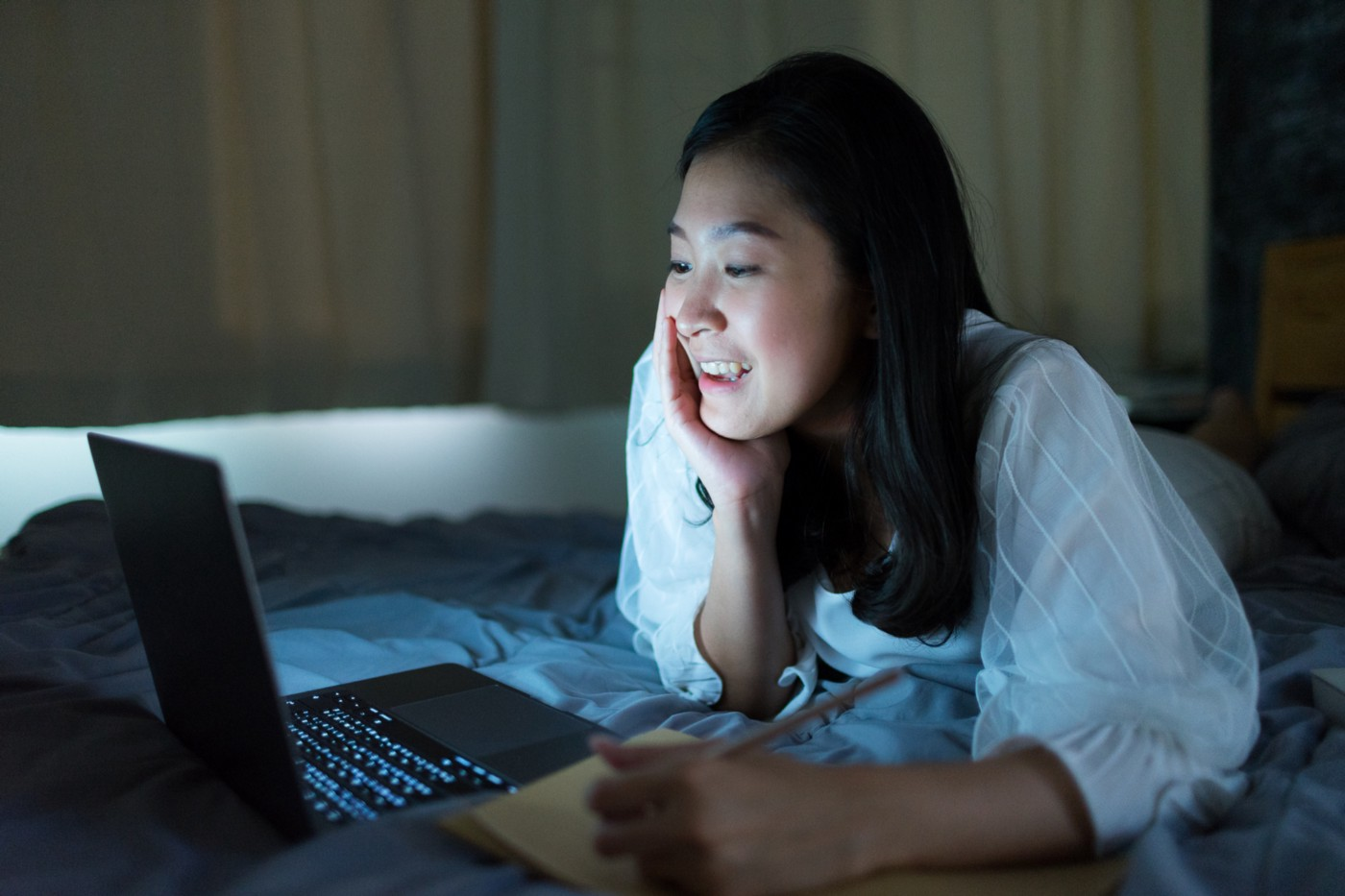 Asian woman writing a note while looking at her laptop with a smile.