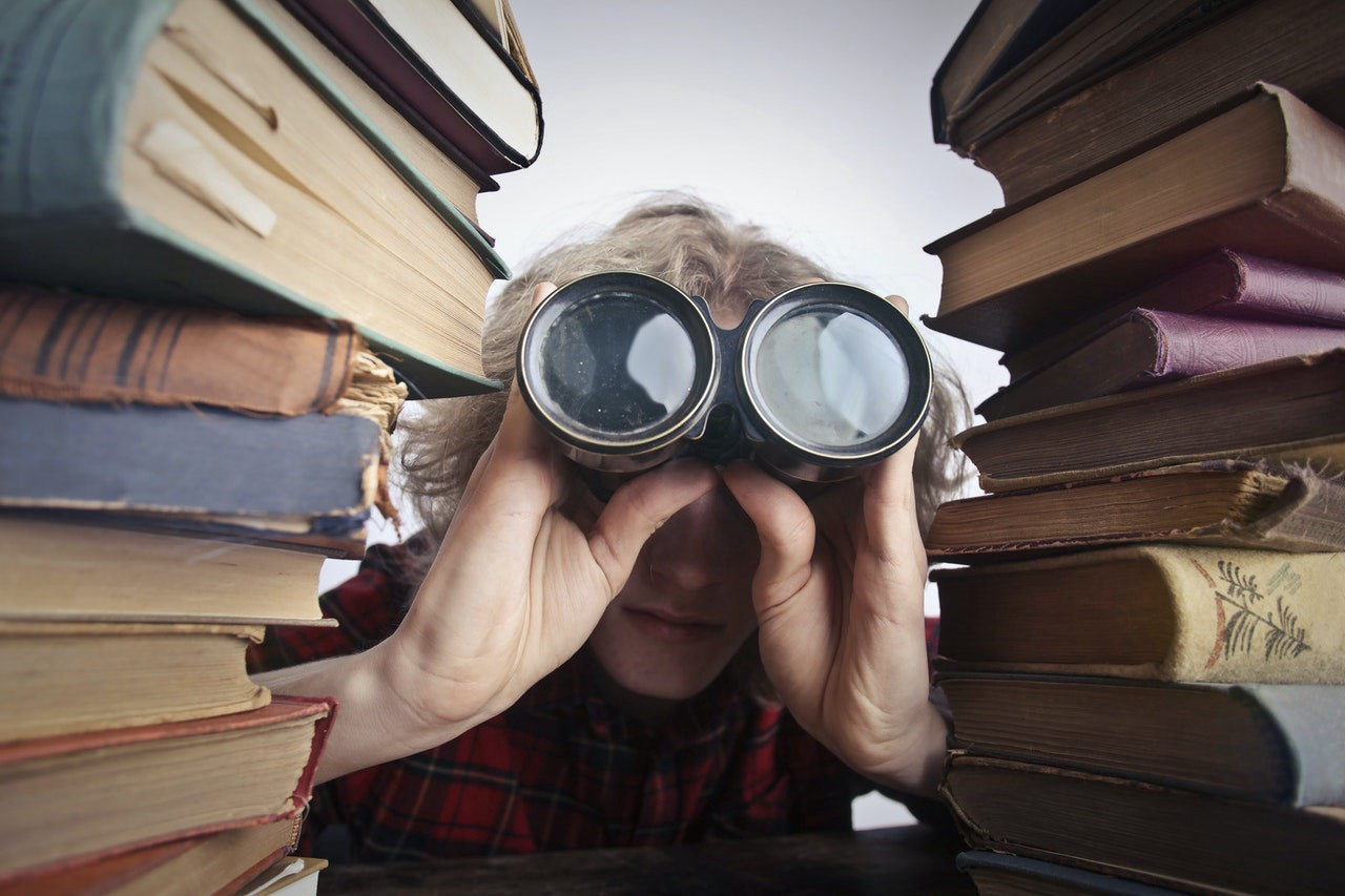 A person looking through binoculars in between stacks of books.