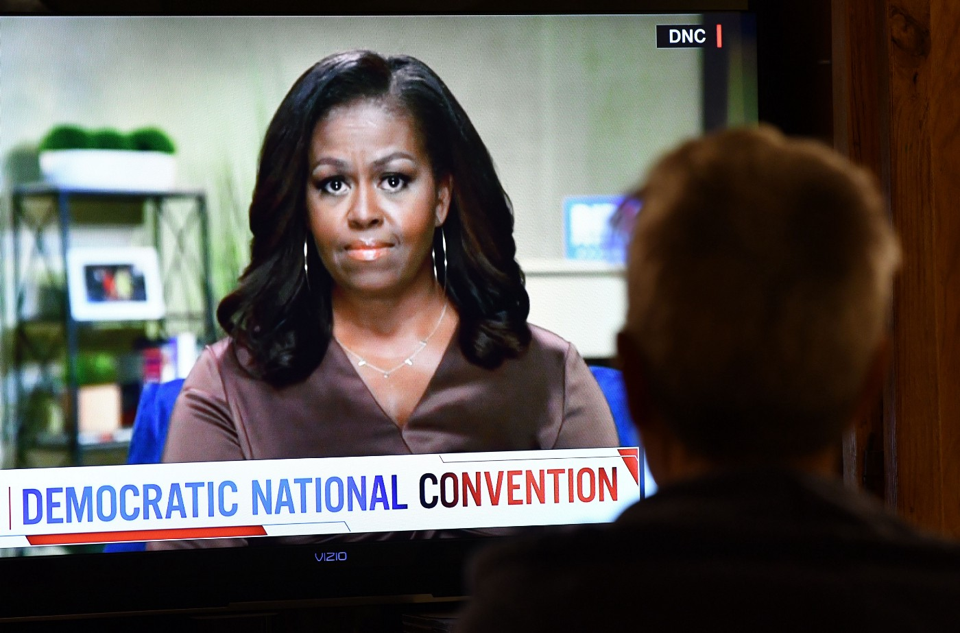 A person watches former First Lady Michelle Obama speak during the opening night of the Democratic National Convention.