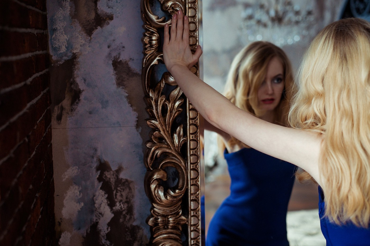 A woman admires herself in a mirror. She has blonde hair and wears a blue dress