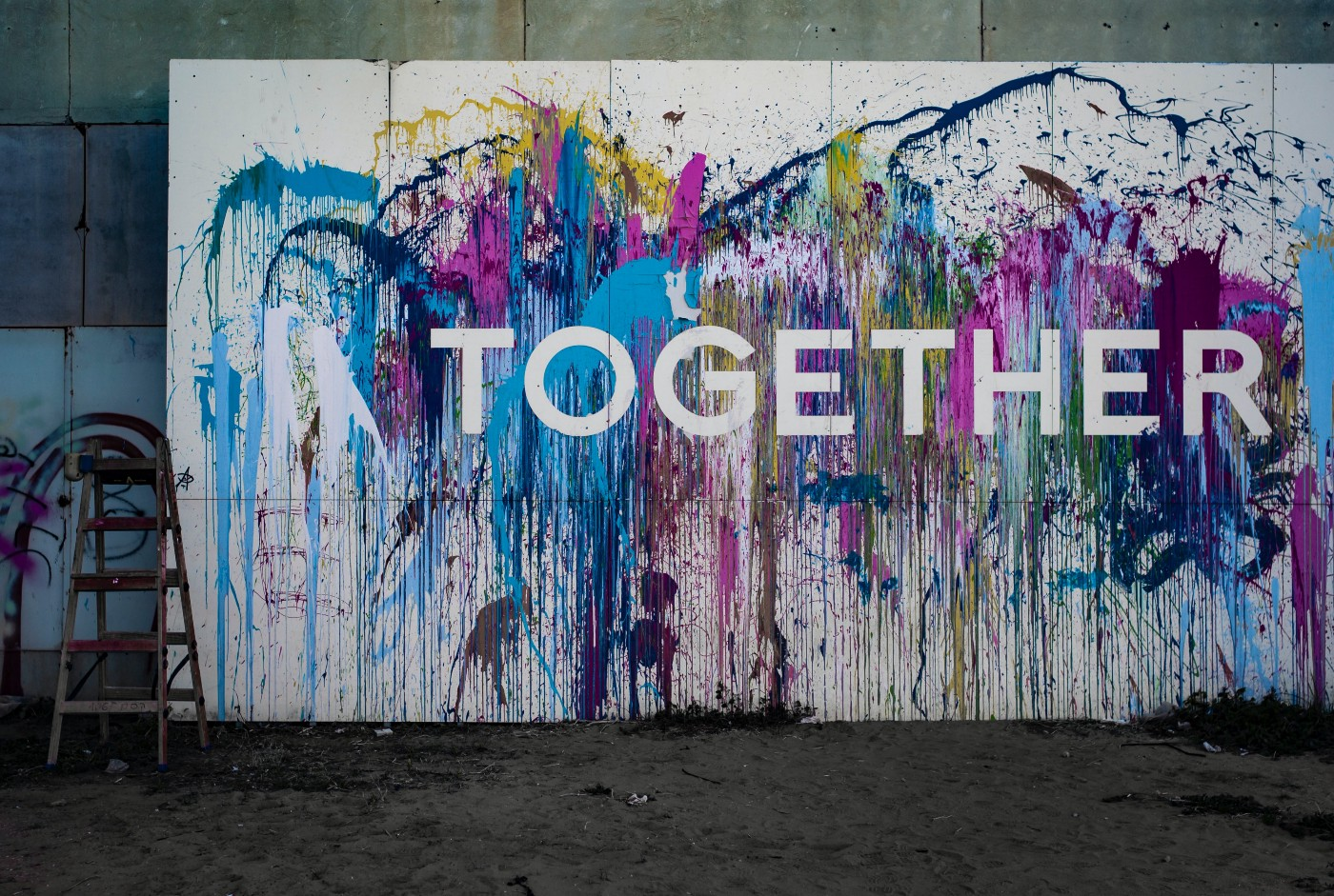 Pale blue, deep indigo, yellow and magenta paint are splashed onto a large white board, with the word 'TOGETHER' on it.