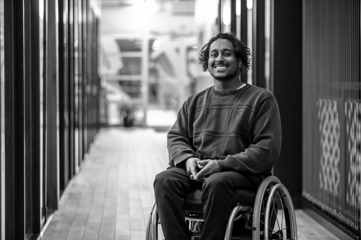 A black man faces the camera and smiles. He is wearing a dark sweater and pants and sitting in a partially visible wheelchair