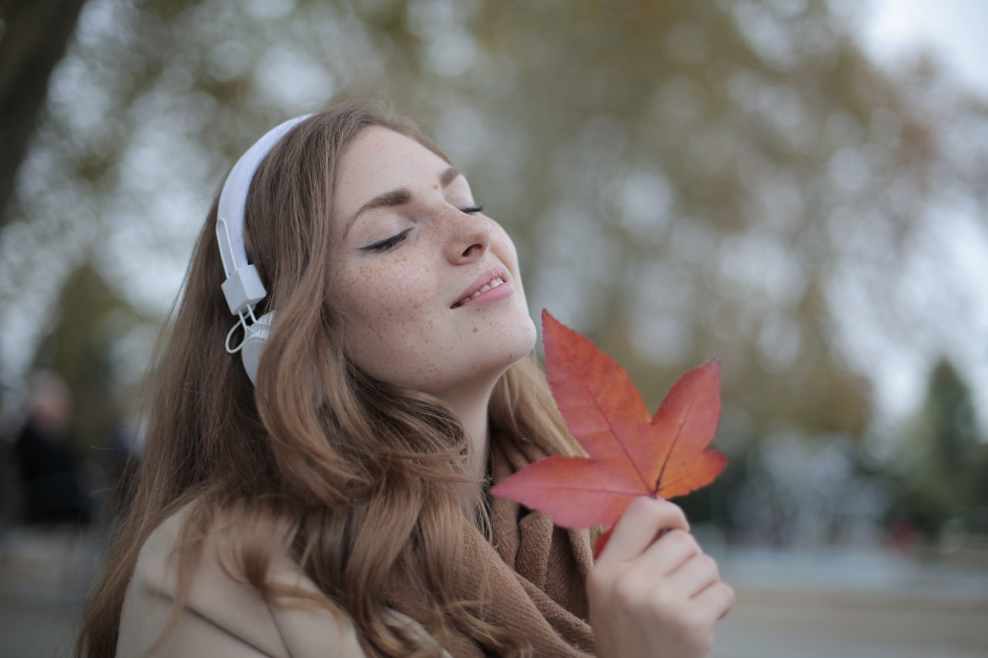 A smiling woman holds a leaf while listening to music
