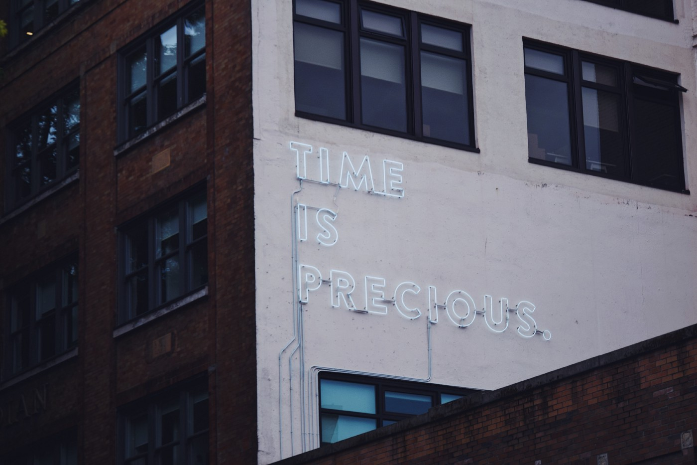 "Neon sign on a side of a building, ""time is precious"""