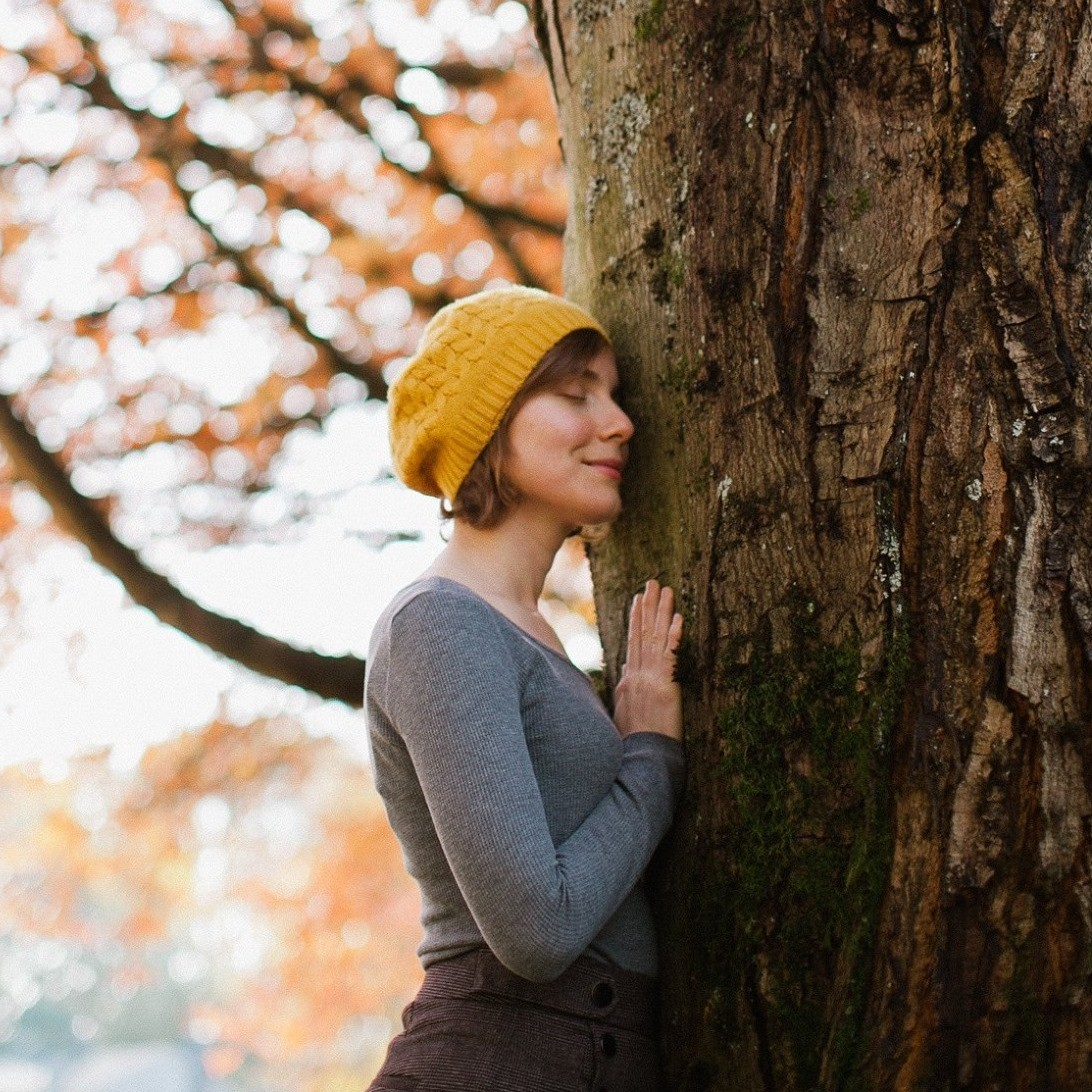 Woman gently sensing and caressing a tree with her eyes closed.