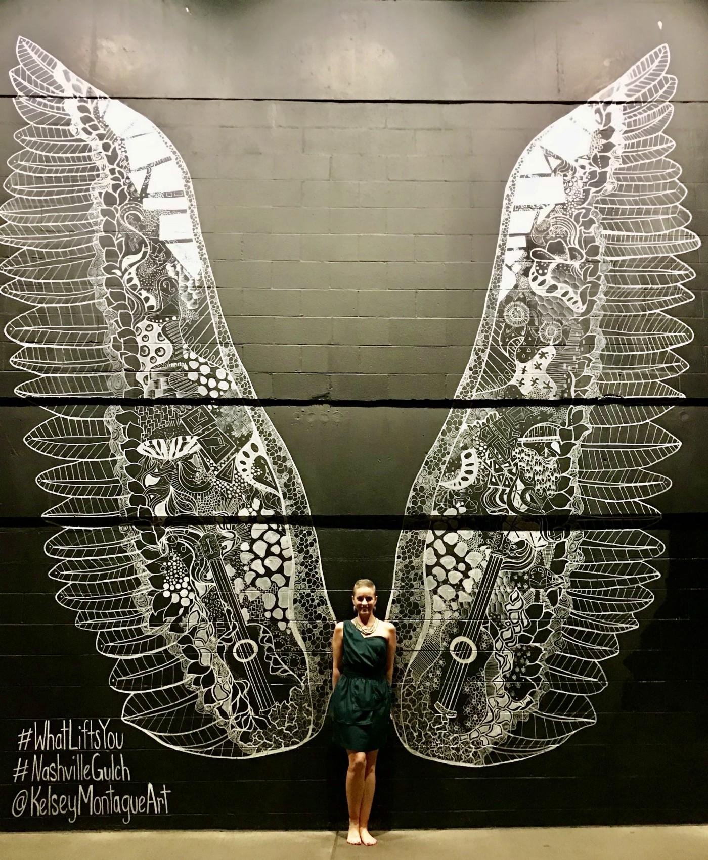 A photo of the author's wife in front of a wall painting of wings.